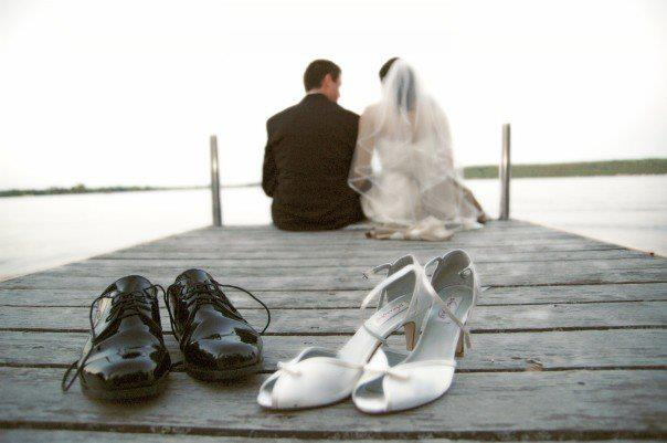 Image of a couple who got married sitting on the dock